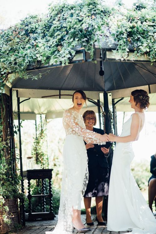 Outdoor wedding ceremony with bride in appliqué wedding jumpsuit and bride in embellished low back dress