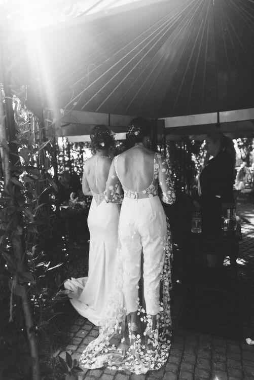 Back of brides appliqué wedding jumpsuit and elegant embellished dress at secluded woodland wedding