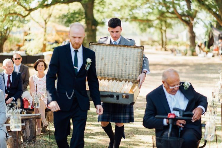 Vintage suitcase with flower confetti at outdoor woodland celebration in autumn
