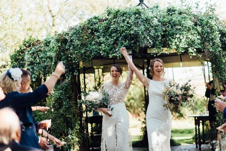 Two brides at same sex wedding at outdoor ceremony with gypsophila  decor