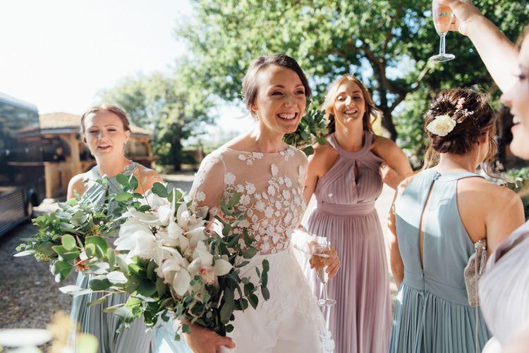 Woodland celebration with pastel bridesmaid dresses and appliqué bridal jumpsuit