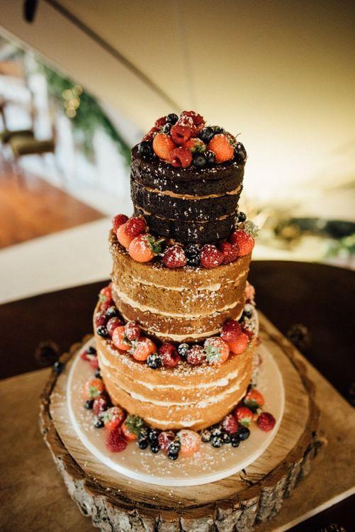 Naked wedding cake with fruit decoration at woodland reception
