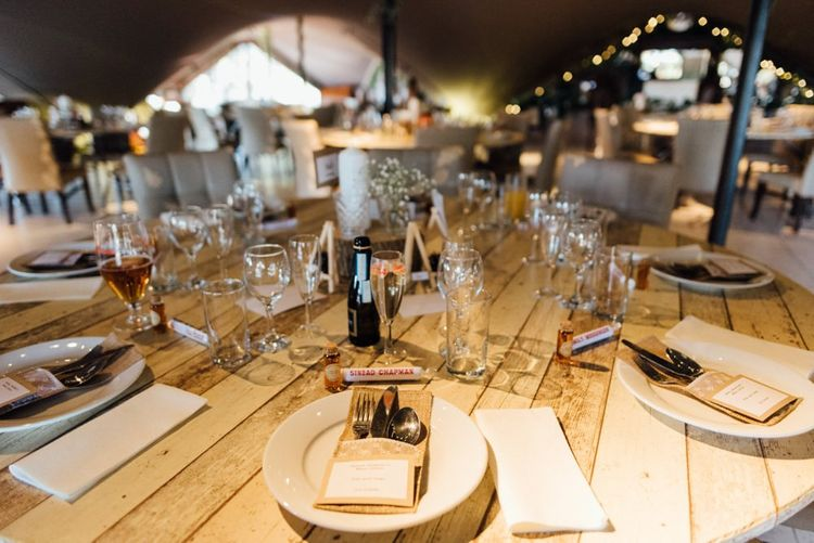 Table decorations kept simplistic with  personalised love heart place settings at woodland styled venue