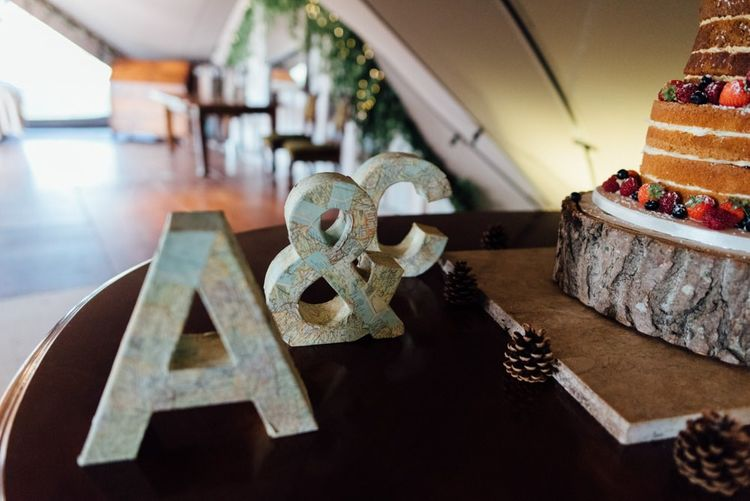 Personalised letter signs next to naked  cake with pinecones at woodland celebration