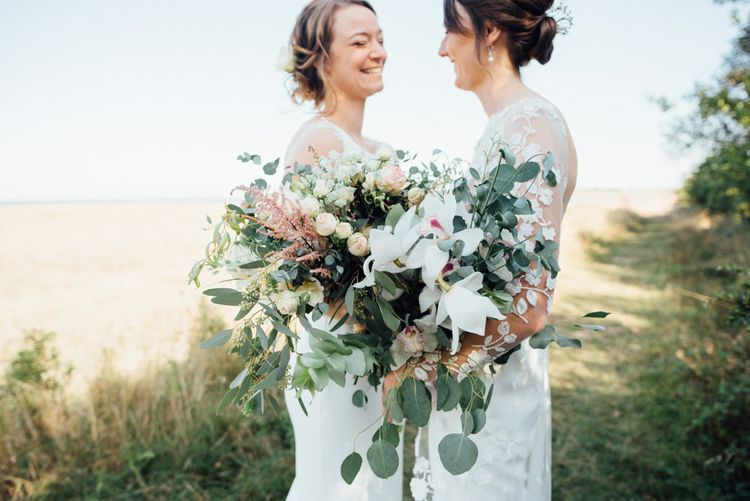 Outdoor autumn woodland celebration with two bridal bouquets