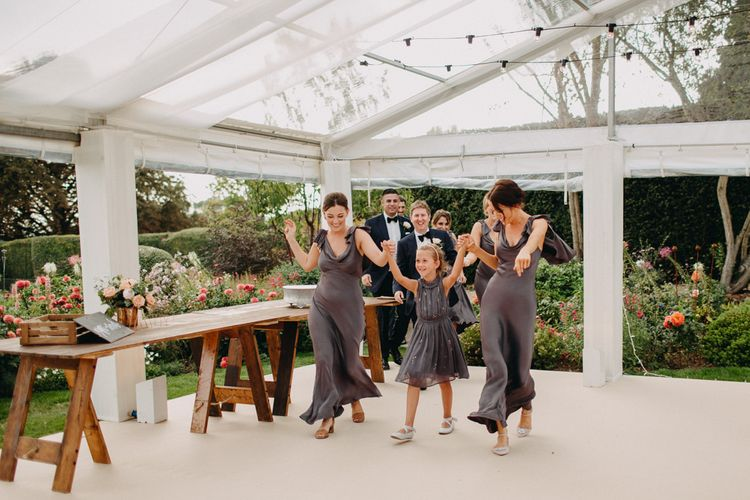 Bridal Party Entrance | Flowers from Topiary Tree | Bride in Karen Willis Holmes | Groom in Custom Made Suit by Suit Supply | Summer Wedding at Family Home in Kent | Glass Marquee from Academy Marquees | Frances Sales Photography