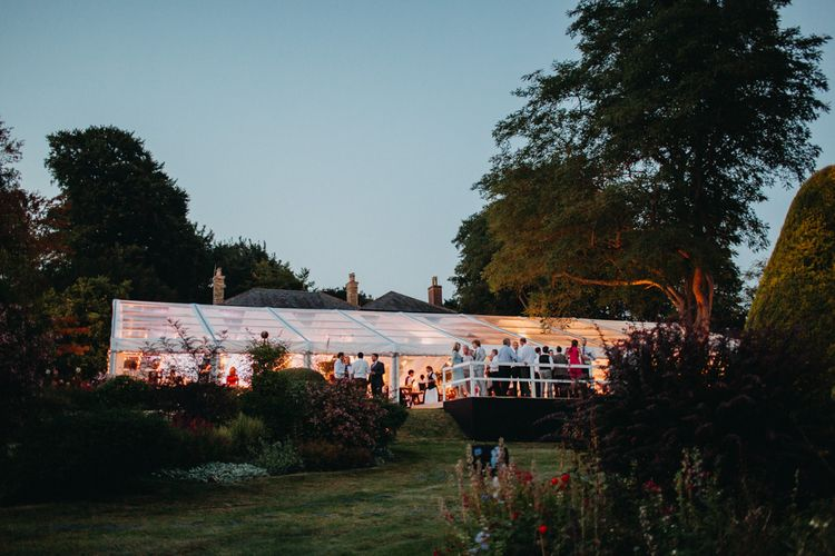 Marquee at Night | Flowers from Topiary Tree | Bride in Karen Willis Holmes | Groom in Custom Made Suit by Suit Supply | Summer Wedding at Family Home in Kent | Glass Marquee from Academy Marquees | Frances Sales Photography