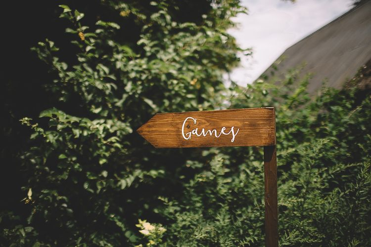 Wooden Direction Sign with White Calligraphy Writing