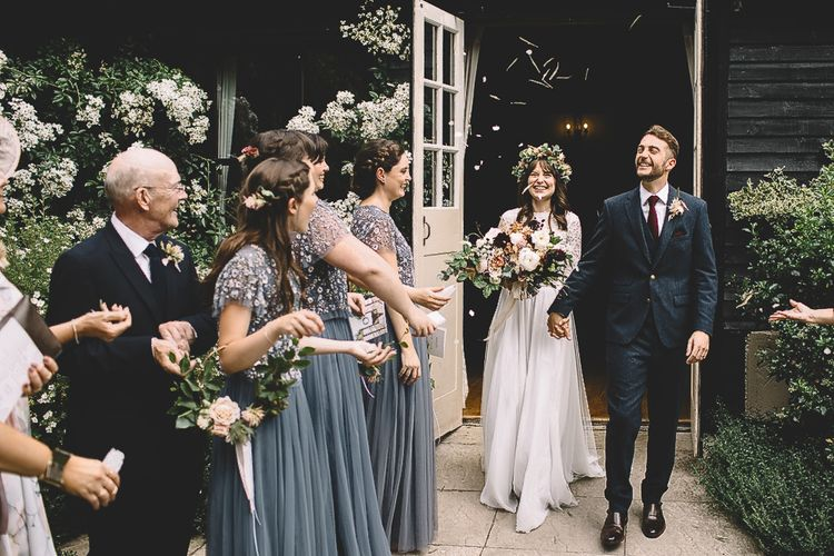 Bridesmaids in Dusky Blue Needle & Thread Dresses Waiting to Throw Confetti Over the Bride in Long Sleeve Lace  Wear Your Love Wedding Dress and Flower Crown and Groom in  Navy Moss Bros. Suit