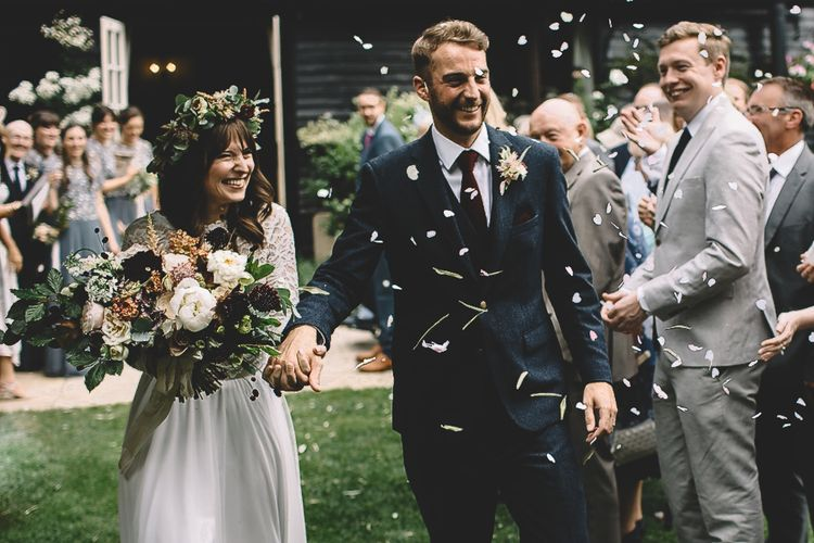 Confetti Moment with Bride in Long Sleeve Lace  Wear Your Love Wedding Dress and Flower Crown and Groom in  Navy Moss Bros. Suit
