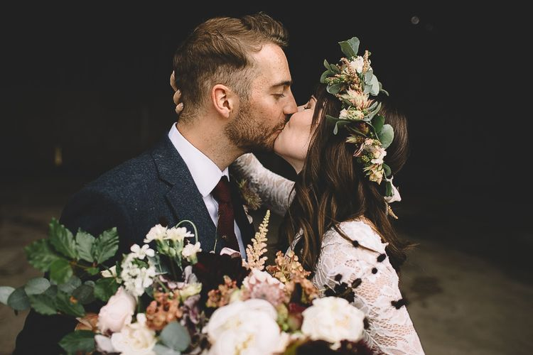 Bride in Long Sleeve Lace  Wear Your Love Wedding Dress and Flower Crown and Groom in  Navy Moss Bros. Suit Kissing