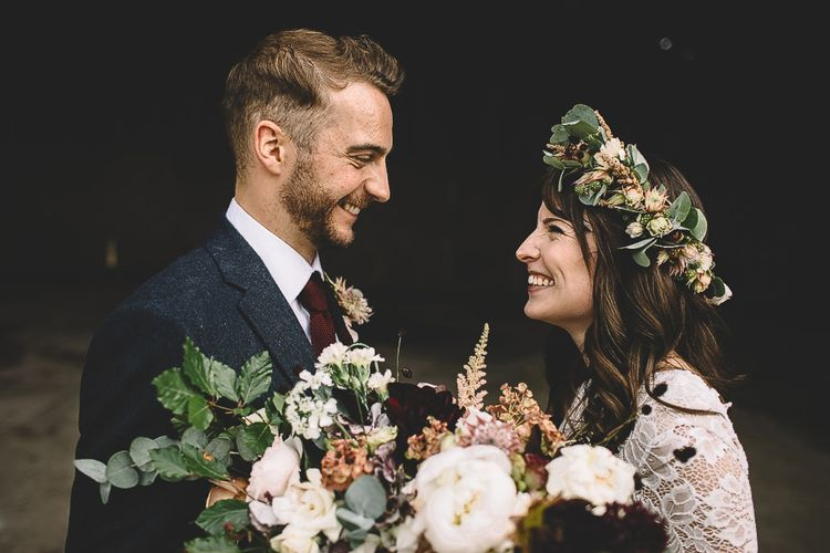 Bride in Long Sleeve Lace  Wear Your Love Wedding Dress and Flower Crown and Groom in  Navy Moss Bros. Suit Laughing