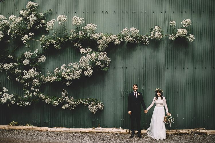 Bride in Long Sleeve Lace  Wear Your Love Wedding Dress and Flower Crown and Groom in  Navy Moss Bros. Suit Holding Hands