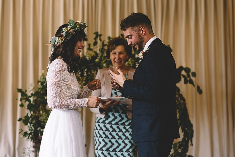Wedding Ceremony with Bride in Long Sleeve Lace  Wear Your Love Wedding Dress and Flower Crown and Groom in  Navy Moss Bros. Suit Saying Their Vows