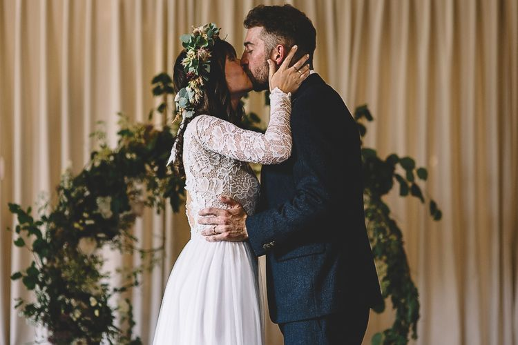 Wedding Ceremony with Bride in Long Sleeve Lace  Wear Your Love Wedding Dress and Flower Crown and Groom in  Navy Moss Bros. Suit  Kissing