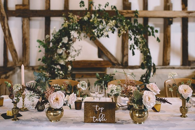 Top Table Wedding Decor with Wooden sign, Flowers in Gold Vessels and Floral Moon Gate Backdrop