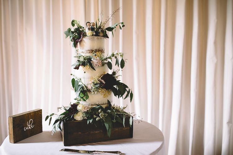 Semi Naked Wedding Cake with Wild Flower Decor on Wooden Crate Cake Stand