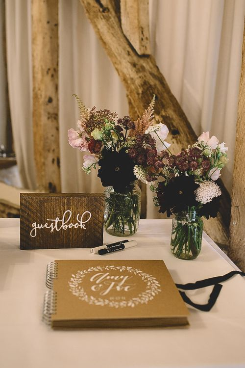 Wooden Guest Book Sign with Craft Paper Guest Book and Wild Flowers in Glass Jars