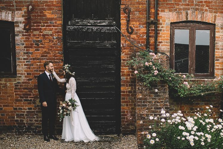 Bride in Long Sleeve Lace Wear Your Love Wedding Dress and Flower Crown Holding Her Groom  in Navy Moss Bros. Suit Face
