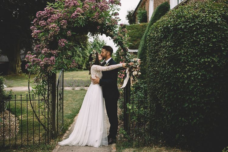 Bride in Long Sleeve Lace Wear Your Love Wedding Dress and Flower Crown and Groom  in Navy Moss Bros. Embracing