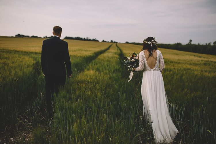 Bride in Long Sleeve Lace Wear Your Love Wedding Dress and Flower Crown and Groom  in Navy Moss Bros. Walking Through a Field