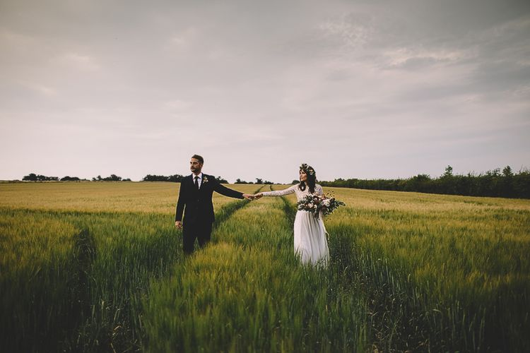 Bride in Long Sleeve Lace Wear Your Love Wedding Dress and Flower Crown and Groom  in Navy Moss Bros. Holding Hands in a Field