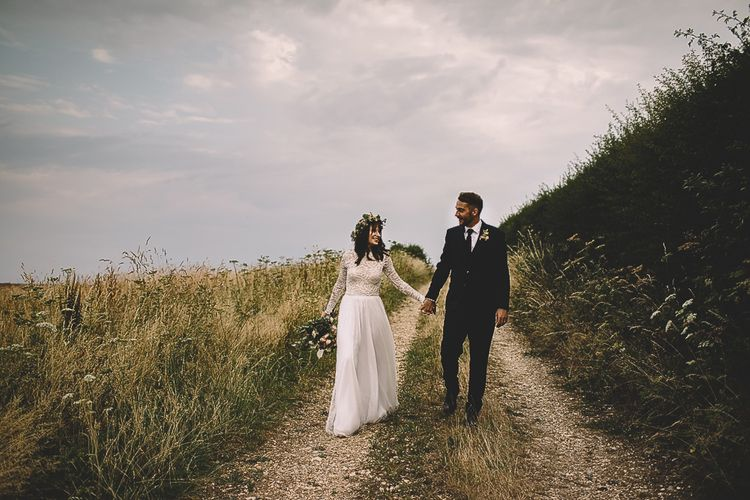 Bride in Long Sleeve Lace Wear Your Love Wedding Dress and Flower Crown and Groom  in Navy Moss Bros. Holding Hands in Country Lane