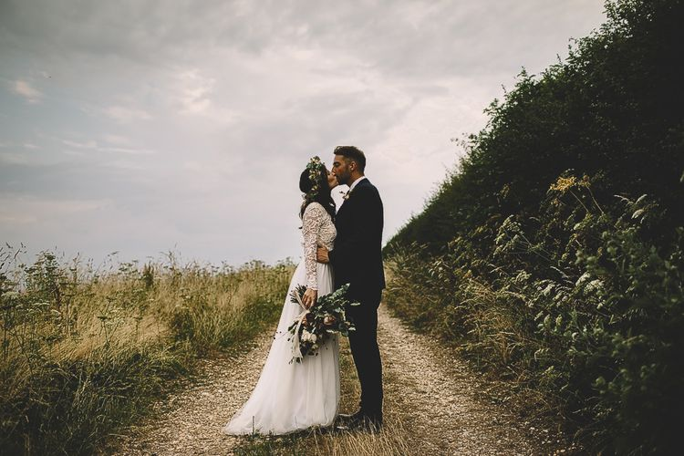 Bride in Long Sleeve Lace Wear Your Love Wedding Dress and Flower Crown and Groom  in Navy Moss Bros. Kissing in Country Lane