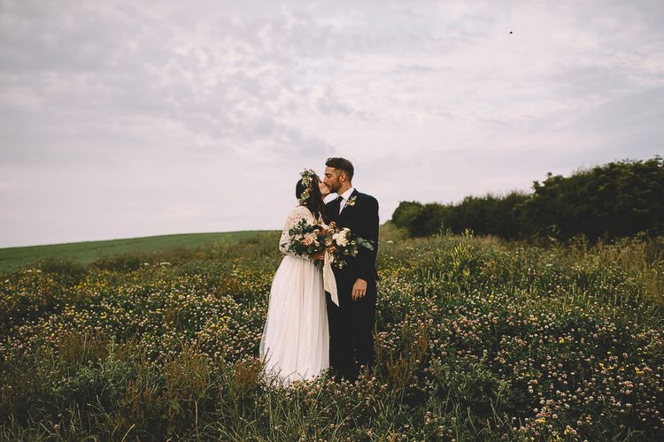 Bride in Long Sleeve Lace Wear Your Love Wedding Dress and Flower Crown and Groom  in Navy Moss Bros. Kissing in a Field