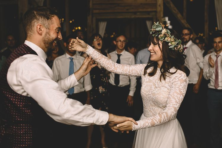 Bride in Long Sleeve Lace Wear Your Love Wedding Dress and Flower Crown and Groom  in Navy Moss Bros.  Suit Laughing During First Dance