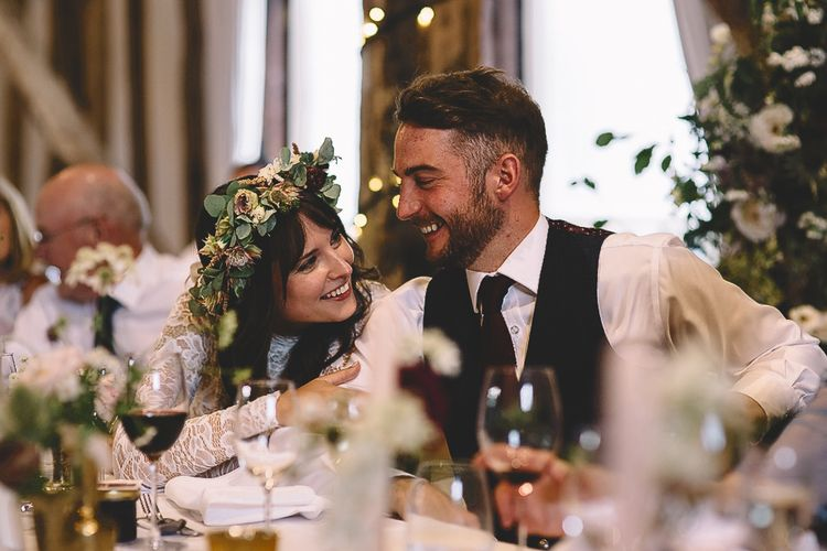Bride in Long Sleeve Lace Wear Your Love Wedding Dress and Flower Crown and Groom  in Waistcoat Laughing and Smiling During Wedding Speeches