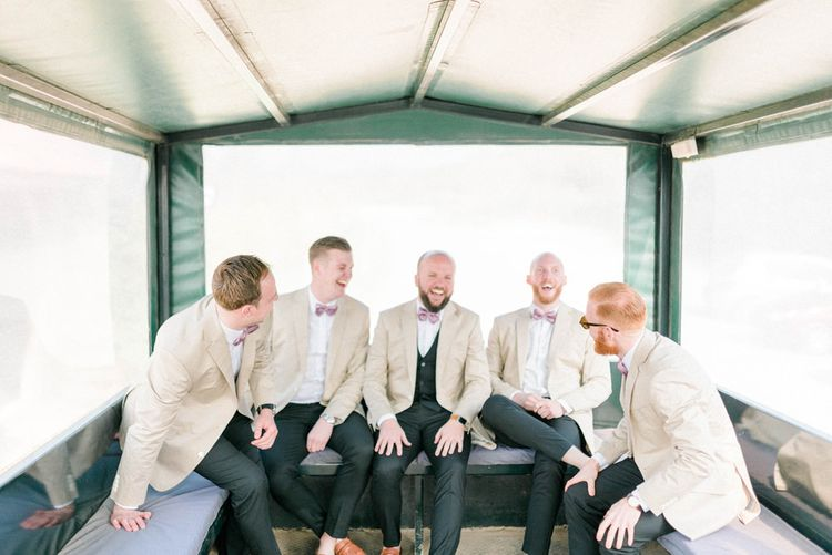 Groomsmen in Beige Jackets and Bow Ties on the Back of a Tractor