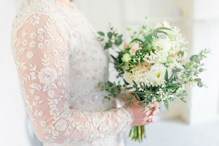 Bride in Needle and Thread Embellished Wedding Dress with Long Sleeves Holding a White and Green Wedding Bouquet