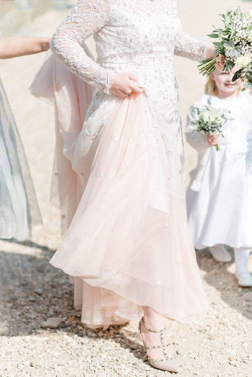 Bride in Pink Ombre Needle & Thread Wedding Dress Holding Up Her Tulle Skirt To Reveal Her Valentino Rock Stud Shoes