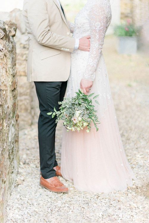 Groom in Black Chino's and Beige Blazer with Tan loafers and Bride in an Ombre Wedding Dress Holding a Bouquet by Her Side