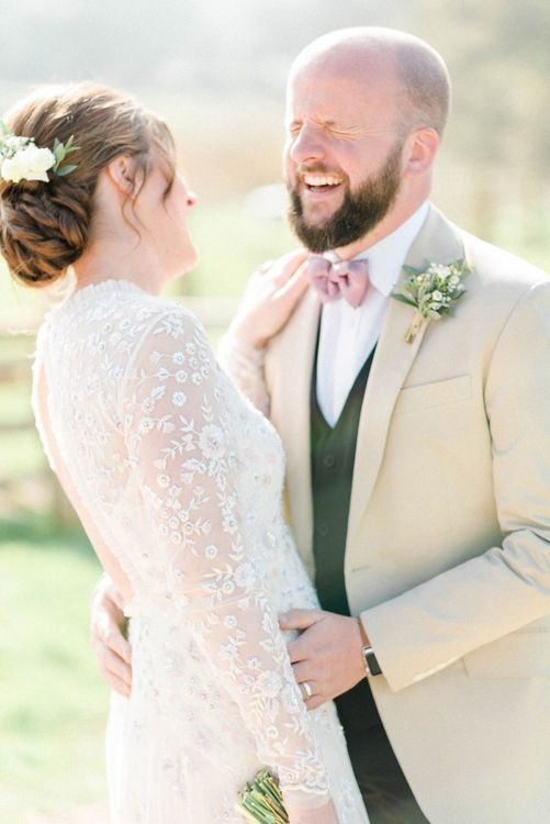 Bride in Needle & Thread Wedding Dress and Groom in Beige Blazer and Pink Bow Tie Laughing Together