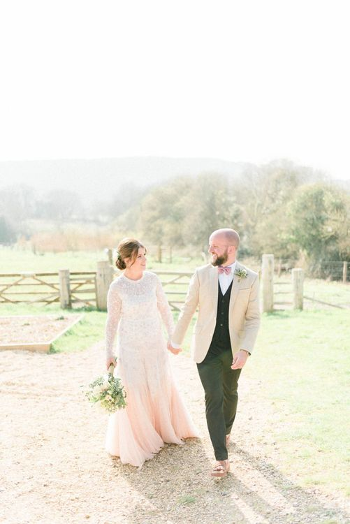 Bride in Needle & Thread Wedding Dress and Groom in Beige Blazer and Pink Bow Tie Holding Hands