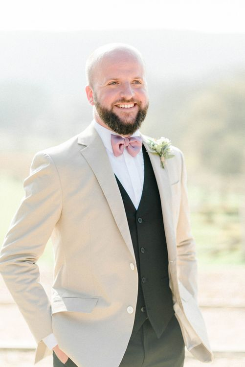 Groom in Black Suit with Beige Blazer and Pink Bow Tie