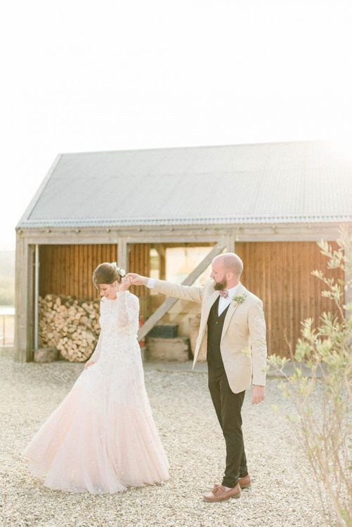 Groom in Beige Blazer and Pink Bow Tie Twirling His Bride in a Needle & Thread Pink Ombre Wedding Dress