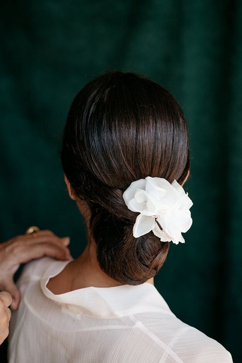 Sleek bridal undo with floral hairpiece
