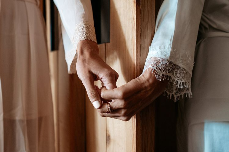 Brides hold hands round curtains at same-sex wedding