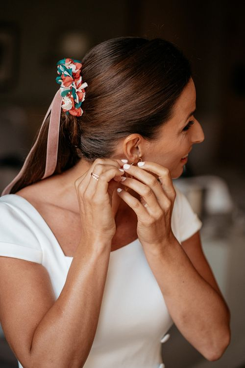 Bridal preparation with floral hairpiece in ponytail
