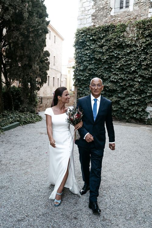 Brides in fitted wedding dresses with Father before outdoor  ceremony