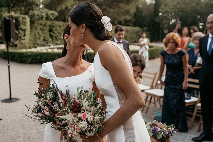Bride greets wife to be at altar in fitted wedding dresses
