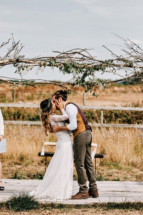 Bride and groom kiss under wooden wedding arch