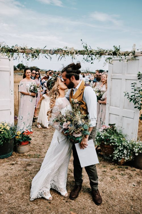Bride and groom kiss at outdoor ceremony with rustic decor and  globe guest book