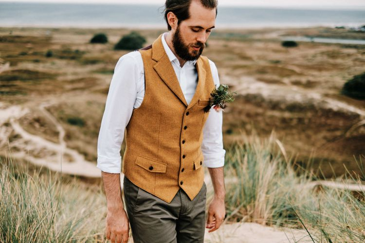 Groom in waistcoat at rustic wedding with globe guest book