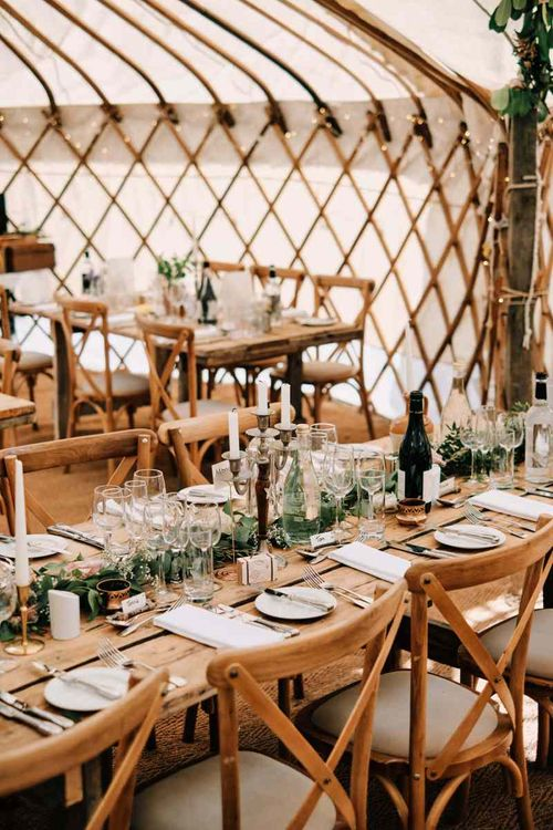 Wedding table decor in yurt with rustic globe guest book
