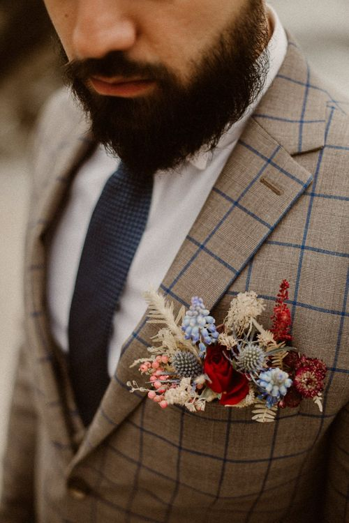 Colourful buttonhole with red and blue and natural grasses