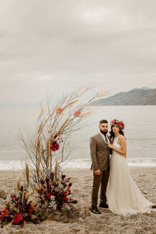 Boho beach elopement with natural floral arrangement and lace wedding dress